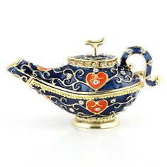 """""""Blue Genie Aladdin Lamp Trinket Box Item No. KB00116A01 $30.09 Make a wish on this blue Genie lamp trinket box. This Faberge style trinket box is constructed from a pewter base. The box is hand enameled, and decorated with Austrian crystals. This box is hinged, and features a magnet for a clasp. The magnet enables the box to open easily, but close firmly. The box is great just for display, for holding or giving as a gift a small piece of jewelry, or for some of your memorable items. Genie Aladdin, Aladdin Lamp, Red Robin Bird, I Dream Of Genie, Moroccan Party, Genie Lamp, Genie Bottle, Pretty Box, Jewel Box"""