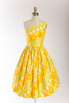 1950s vintage dress in a bold and bright yellow, orange and green printed cotton. Fitted waist, sculpted bust with one shoulder strap. Darting at bust and waist for fit. Full gathered skirt with pipin