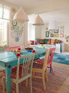 eclectic dining room, blue table, mixed chairs, plate wall, striped rug