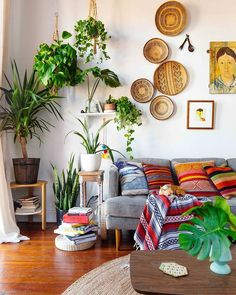 Amazing boho living space with global textiles, lots of greenery and woven baskets as wall art. Delightful.