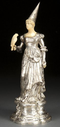 A CONTINENTAL SILVER AND CARVED IVORY FIGURE OF A MEDIEVAL MAIDEN, CIRCA 1900. Well modeled and chased with a finely carved ivory head and shoulder surmounted with a conical silver cap, inset carved ivory hands and holding a faux ivory carved falcon, the figure raised on a wasted quatrefoil plinth, stamped hallmarks. Height 10.75 inches (27.5 cm).