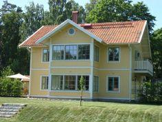 Gult hus. Rött tak. Inglasad balkong och veranda.