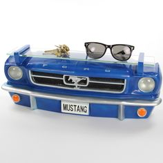 Designed like the front end of a blue 1964-1/2 Mustang, this decorative wall shelf makes a fun and unique way to hold tools, collectibles and other gear in your garage or home. Made of poly-resin with a tempered glass shelf. Has working lights (3 AA batteries, not included). An amazing gift for anyone who loves muscle cars. Hand-painted, and mounting holes make hanging a breeze. Measures 19 Wall Shelf Decor, Wall Shelves, Glass Display Shelves, Hanging Lights, Car Parts, Ford Mustang, Muscle Cars, Man Cave, Kids Room