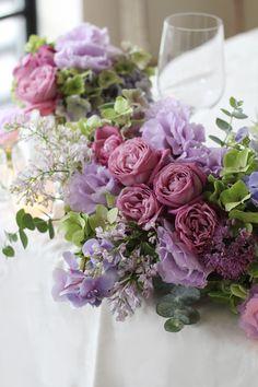紫をメインカラーにした気品ある会場装花。 赤紫の丸いバラとフリルが美しいリシアンサス(トルコキキョウ)、ほんのり香るライラック等、様々なパープルを合わせてまるで水彩画のような色合いに。 またグリーン〜ブルー〜パープルのグラデーションが美しい秋色アジサイやユーカリなどのシルバーグリーンも合わせることで、全体を優しく大人っぽくまとめています。 August Wedding Flowers, August Wedding Colors, Floral Wedding, Beautiful Bouquet Of Flowers, Amazing Flowers, Purple Flowers, Purple Flower Arrangements, Wedding Arrangements, Wedding Flower Decorations