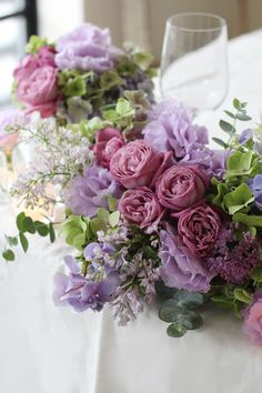 紫をメインカラーにした気品ある会場装花。 赤紫の丸いバラとフリルが美しいリシアンサス(トルコキキョウ)、ほんのり香るライラック等、様々なパープルを合わせてまるで水彩画のような色合いに。 またグリーン〜ブルー〜パープルのグラデーションが美しい秋色アジサイやユーカリなどのシルバーグリーンも合わせることで、全体を優しく大人っぽくまとめています。