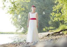 Hochzeitskleid mit trägern, überschnittenen schultern und rundem ausschnitt, gürtel mit rot und pink, leicht ausgestellter rock in a- linie, fascinator mit roten und pinken fächerblumen und hutschleier (Foto: Hanna Witte) (http://www.noni-mode.de)