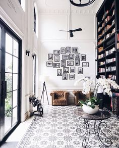 black and white foyer with great gallery art wall and floor to ceiling bookcase