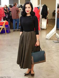 Street Style by Dita Von Teese.  She wears a New Look tweed skirt with soft box pleats, paired with a black bombshell sweater and black flats.