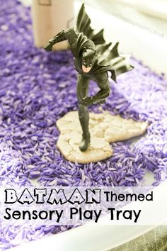 Batman sensory play tray set up with coloured rice, cardboard tube buildings and Batman superhero figures