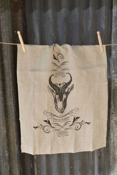 A generously sized stonewashed linen cloth, printed with a hand drawn tongue-in-cheek design of South Africa's favourite buck.  Manufactured in India and imported by Masquerade Printed in South Africa Made from 100% linen, woven from Belgium linen flax Enzyme washed (stone washed) to enhance the soft and floppy texture Product detail: – 2cm hem with pulled thread detail on one end – Size: 50cm x 70cm – Colour option: pure white or natural linen Designed by and exclusive to Masquerade