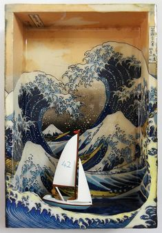 """""""The Meaning of Life"""" by Hogret - collaged combinations of 3 versions of Hokusai's wave etchings, distress inks, resin, miniature yacht with two figurines (HO Gauge)."""