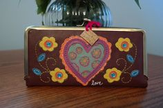 "This would make a great Valentines Day gift for any women!  Natural Life Leather Vegan Wallet Heart Sign and Love,  Includes 6 cardholders, 2 cash pockets, ID window, zippered pocket and built in mirror Vegan leather with pink satin lining     8"" W x 3 3/4"" H Purchase for just $26.00 This gift item ships for just $5.25 when purchased by itself. (http://www.inspirationalgiftstore.com/natural-life-leather-vegan-wallet-heart-sign-and-love/)"
