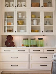 """Kitchen - I dream of plenty of storage and glass cabinets to display the playful colors of my dish collection - a beautiful contrast for the clean white background of the cabinets. Of course, I couldn't help but notice the beautiful green jars and the large """"&""""which I interpret to mean togetherness, just like the mugs with the family members' initials, all hanging out together on the top shelf."""