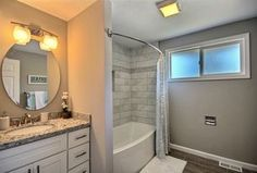 Contemporary Full Bathroom with tiled wall showerbath, Undermount Sink, specialty tile floors, Vanity 2 Light Vanity Light