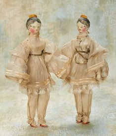 "* Very Rare Pair of Grodnertal Wooden Tuck Comb Ladies with Original Costumes 9"" (23 cm.) Each is all-wooden with one-piece head and torso,elongated throat,shapely bodice,carved wooden yellow tuck comb at the crown,painted black hair with shaded edging and exaggerated spit curls,original wooden earrings,painted facial features and blush,dowel-jointing at shoulders,elbows,hips and knees,painted orange shoes"
