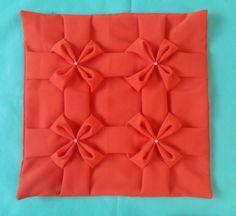 Capa de almofada com capitonê 4 laços na frente e costas liso. Tecido: Oxford. Cor: laranja (pode ser confeccionada em outras cores sob encomenda). Este preço não inclui enchimento.