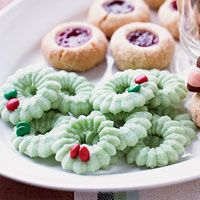 These buttery spritz cookies are dyed green and shaped like wreaths for a fun and festive holiday cookie.
