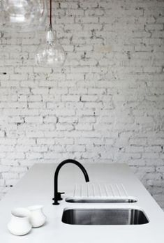 Love the grungy Industrial look of this kitchen with the 30 coast of paint on the old brick wall, the black faucet and the industrial pendant lighting Deco Design, Küchen Design, House Design, Loft Design, White Brick Walls, White Bricks, Modern Kitchen Design, Minimal Kitchen, Exposed Brick