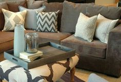 Chocolate brown couch and throw pillows.. a coffee table and extra seating when needed