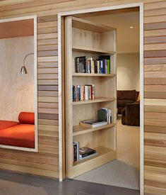 With a gentle push, this cedar bookshelf in a Washington house swings in to reveal a large media room equipped for sleeping and movie-watching, with couches and a Murphy bed. -- Dwell