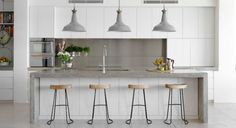 If you're convinced a sleek, white kitchen is still for you, you'll need to bring it down to earth for it to work well with concrete. Even small touches of natural timber can prevent it from feeling sterile – in this case, the stools, bread board and wooden spoons.   Tip: Displaying fruit, leafy herbs and flowers can breathe life into any kitchen, no matter how minimalist or industrial its design.