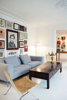 Creative gallery wall spices up the living room together with a massive and dark wooden coffee table - great contrasts.