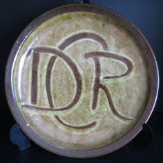 These were made to fund his railway project DCR stands for Driving Creek Railway Here is his mark although one 'spoke' is missing due to placing it on the curve Pottery Marks, Ceramics, Studio, Food, Plate, Pottery, Study, Studios, Clay Crafts