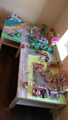 Lego friends city made from 2 ikea coffee tables , cover in paper , paint on green areas roads etc ....shelves under are great for storing mauals and boxes of spare pieces.