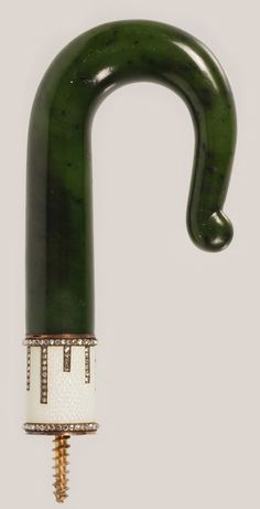 A Faberge gold, gem-set, nephrite, and enamel parasol handle, workmaster Michael Perchin, ST Petersburg, circa 1899-1903. The carved hook-shape nephrite handle banded by a translucent white enamel collar over an engine-turned ground, surrounded by accent bands of mine-cut diamonds, with scratched inventory number 1984.