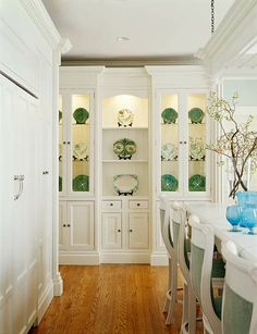 Three cabinets were combined in the butler's pantry to give the appearance of an antique breakfront. Crown molding, beadboard backing in the central unit, flush inset doors and drawers, and deep base moldings combine their decorative power to complete the transformation.     Designer: Shelley Gordon