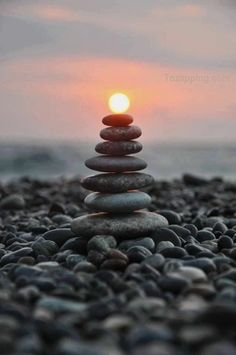 Stacked rocks under a rising sun.