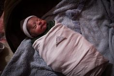 A small folded piece of paper containing a prayer sits on 10-day-old Khaled's chest before he is swaddled by his grandmother, Jalila. The #babies are wrapped in many layers to protect them against the freezing temperatures. UNHCR / A. McConnell / January 2015