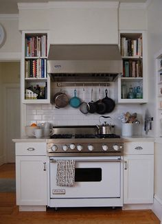 Love the bookshelves next to the hood! The hanging pots are a good idea too. #kitchens #shelves #hardwoodfloors