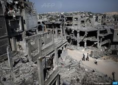 BEIT HANUN : Palestinians walk past destroyed buildings in the northern Gaza Strip city of Beit Hanun on August 22, 2014. The Hamas armed wing declared the truce efforts over after Israel carried out an abortive assassination attempt the previous day on its leader Mohammed Deif, killing his wife and two of his children. AFP PHOTO / THOMAS COEX