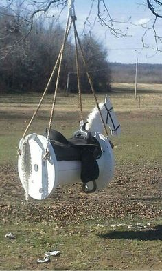 Horse swing made from cable spool with real saddle