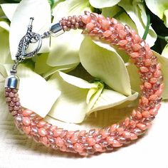 """Luscious Miyuki Japanese magatama glass beads in shades of opaque salmon and tan luster lend their beauty to this Kumihimo braided bracelet I have named """"Shaylee's Dragon"""". I chose this name for the unique way these magatama Japanese beads overlap in a way that mimics scales however, they are very smooth to the touch. Shaylee is an old Irish name meaning """"fairy of the fields"""". Kumihimo braiding is an ancient art and the word """"kumihimo"""", in Japanese, litera..."""