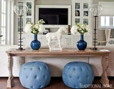 """Giuliana And Bill Rancic's Amazing Home! A pair of blue linen poufs are tucked beneath a sofa table from Hickory Chair in the family room, decorated in classic blue and white. Console table (17th-century Italian Console""""): Hickory Chair."""