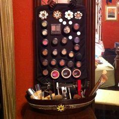 Magnetic eyeshadow/makeup board using a cookie sheet, and a container filled with metallic sand for brushes!