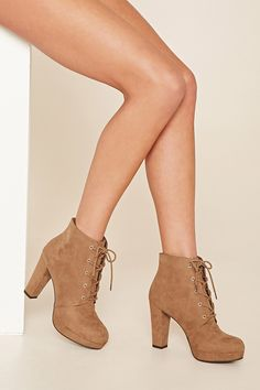A faux suede platform ankle boot featuring a round toe, a lace-up front, and a chunky heel.