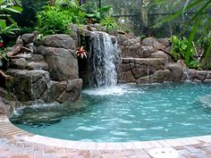 I would love to have a pool with a waterfall and hot tub and tropical landscaping all around it. I could do this to my back yard