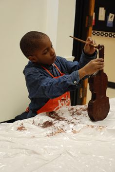 """Every year Conservatory Lab kindergartners—not quite ready for prime time—make their own  instruments—out of paper mache. When playing in a """"paper orchestra,"""" they get the feel of their  instrument and learn to respect it. At the end of school year, the students receive their first, very  own, real instrument."""