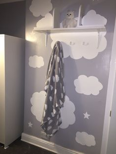 Hand painted clouds and stars on feature wall. Handmade cloud bookshelves. Playroom idea