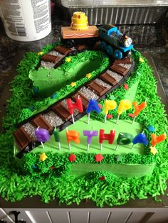 Thomas the Train birthday cake. Carter's second birthday cake. Number 2 cut from double layer sheet cake. Colored coconut green for the bottom and Hershey bars for the tracks.