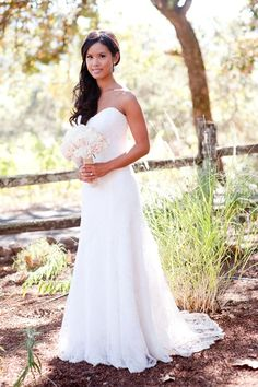 """Jonie attached live ivory lisianthus and garden roses to her softly-curled half-up-half-down big day hairstyle. The soft, natural accessories """"complimented the natural, rustic setting,"""" the bride says."""