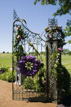 Wreaths of purple hydrangeas and arrangements of moss and roses make for a grand entrance to the ceremony area.