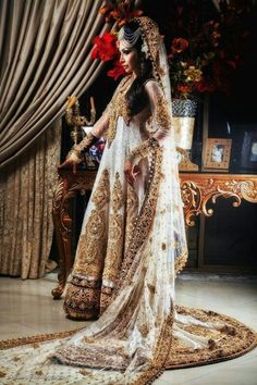Outfit by:Mina Hasan  White and gold indian lengha with hints of navy blue embroidery.