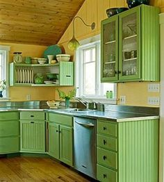 This country cottage kitchen's beadboard cabinets and unique open storage corner shelf standout against the bright yellow walls.  Pine flooring and plank ceiling help tone it down a bit.