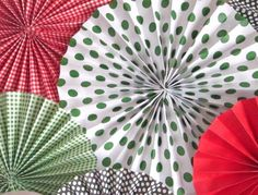 paper fan flowers made with 3 sheets of paper. Could also use as decoration in a baby's room. I've seen people make these in different sizes and make a garland, too. Add decorations to the centers with hot glue.