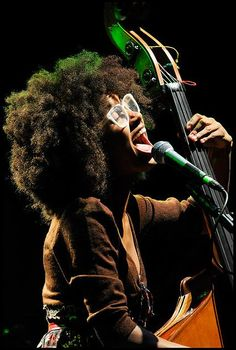 The photo of this naturalista songstress/musician is BEAUTIFUL! Love the big fro + white eyeglasses.