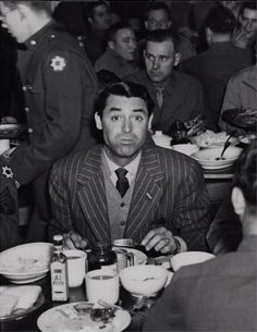 Cary Grant eating and drinking with the soldiers, Camp Crowder, Missouri. c.1942.